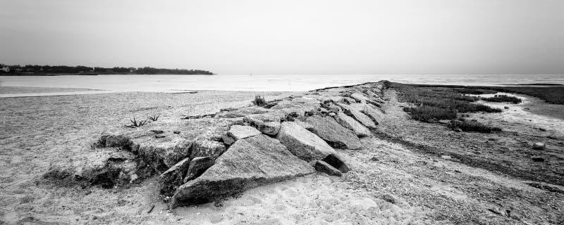 Rocky Pier auf Strand in Schwarzem u. in weißem lizenzfreie stockbilder