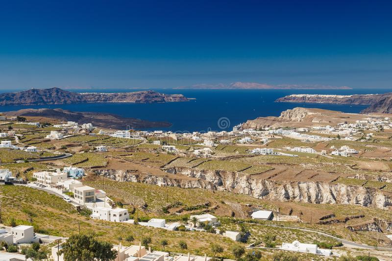 Rocky plateau whith white houses in Greek island Santorini. With blue surface of the sea and other islands in the background royalty free stock photography