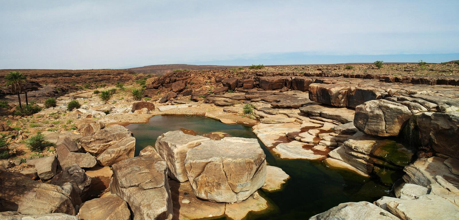 Rocky pond on Adrar plateau, Mauritania. Panorama of rocky pond on Adrar plateau, Mauritania stock image