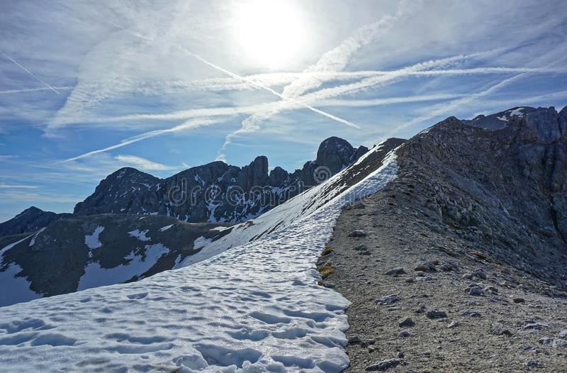 Rocky ridge half covered with snow stock photo