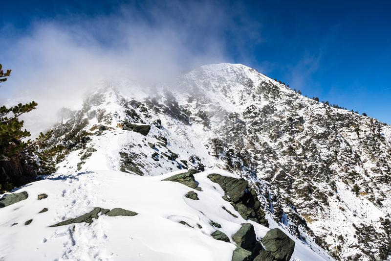 Rocky ridge on the trail towards the top of Mount San Antonio (Mt Baldy) on a snowy but sunny day, with fog rising from the valley. Los Angeles county, south stock images