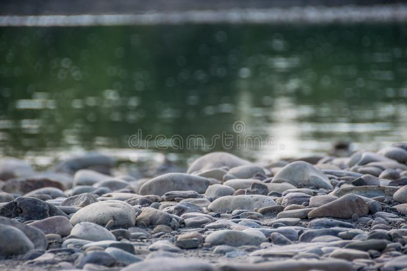 Rocky riverbank. Close-up view of stones behing blurred green water of mountain river at the background royalty free stock images