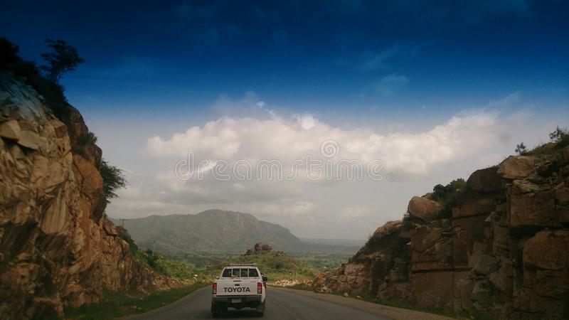 Rocky roads and blue skies. The view on the road to Abuja from Jos, Plateau State, Nigeria stock images