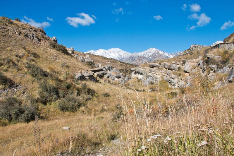Rocky hillsides and dry meadows afford a glimpse of distant mountains stock photos