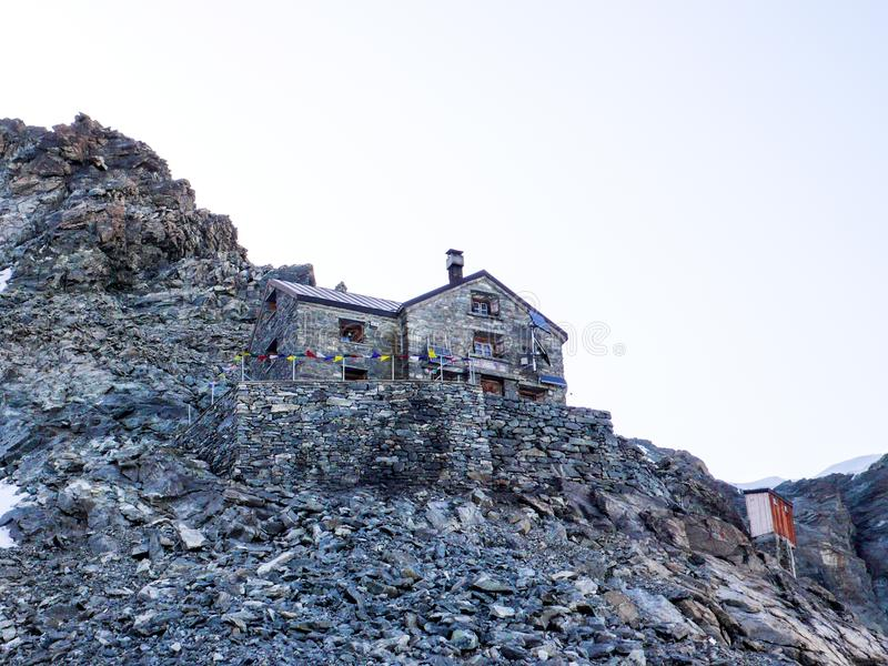Rocky scree slope with a stone mountain hut at the foot of a high alpine peak. Rocky scree slope with a stone mountain hut at the foot of the Dent Blanche royalty free stock photography