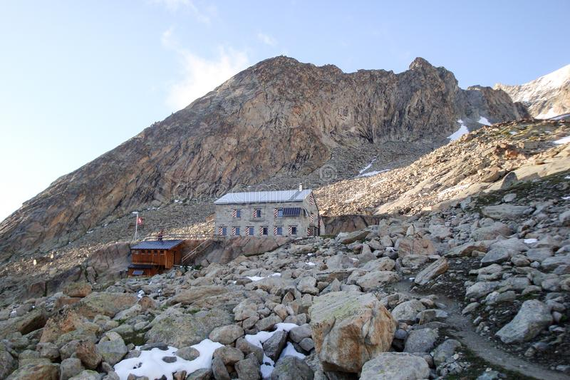 Rocky scree slope with a stone mountain hut at the foot of a high alpine peak. Rocky scree slope with a stone mountain hut at the foot of the Le Mammouth royalty free stock photography