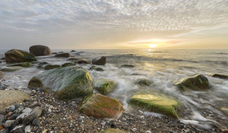 Rocky sea coast, in the light of the rising sun stock photo