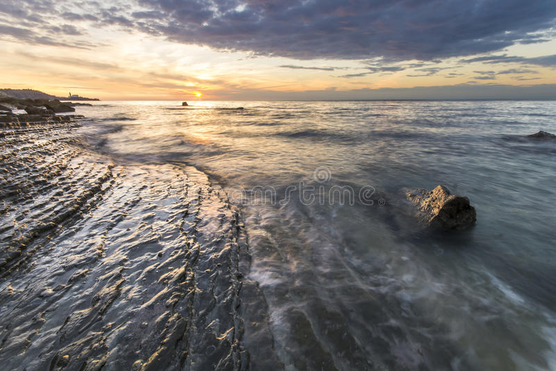 Rocky sea coast, in the light of the rising sun stock image
