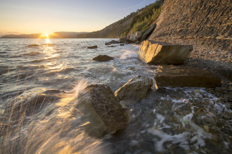 Rocky sea coast, in the light of the rising sun royalty free stock image