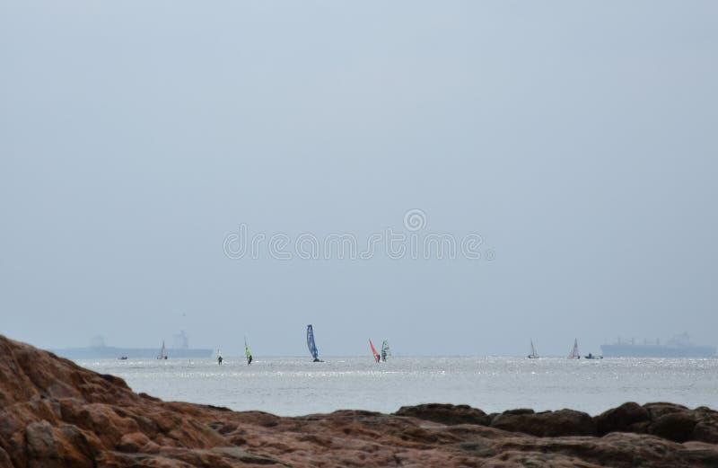 Rocky sea with many windsurfers. In the horizon stock photography
