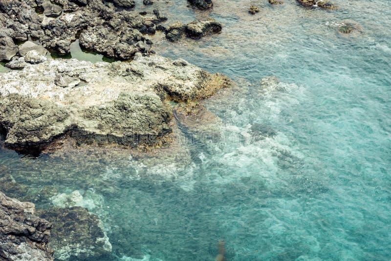 Rocky sea shore of Acitrezza next to Cyclops islands, Catania, Sicily, Italy.  royalty free stock photography