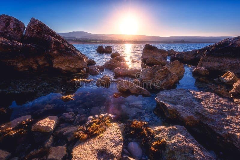 Rocky seacoast at sunrise, Akamas peninsula, Cyprus. Amazing nature seascape with rising sun over the rocky seacoast of Akamas peninsula, Cyprus. Mediterranean royalty free stock photos