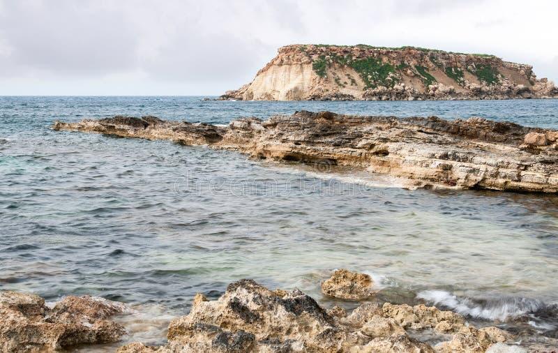 Rocky Seascape con la isla de geronisos imágenes de archivo libres de regalías