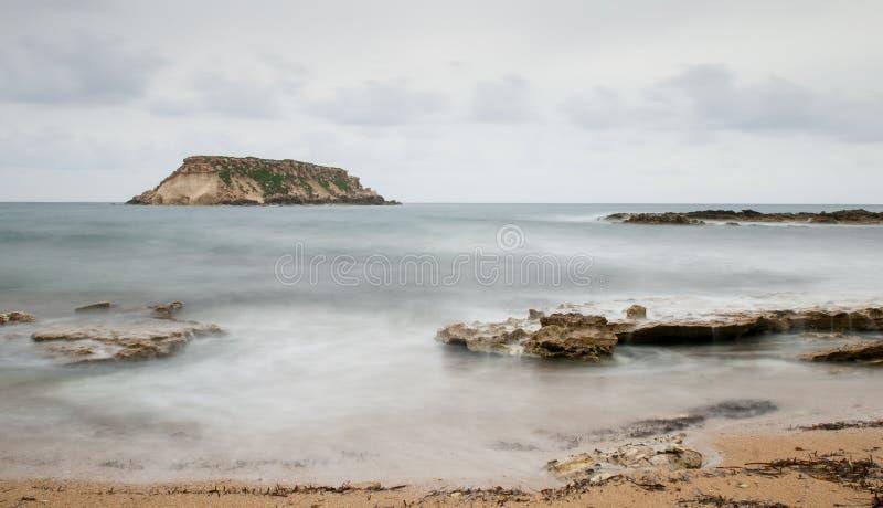 Rocky Seascape con la isla de geronisos fotos de archivo libres de regalías
