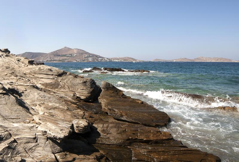 Rocky seashore in Paros island. With waves splasing royalty free stock images