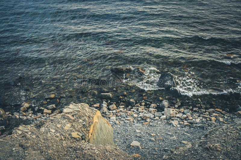 Rocky seashore with a quiet surf. Toned image. royalty free stock photo