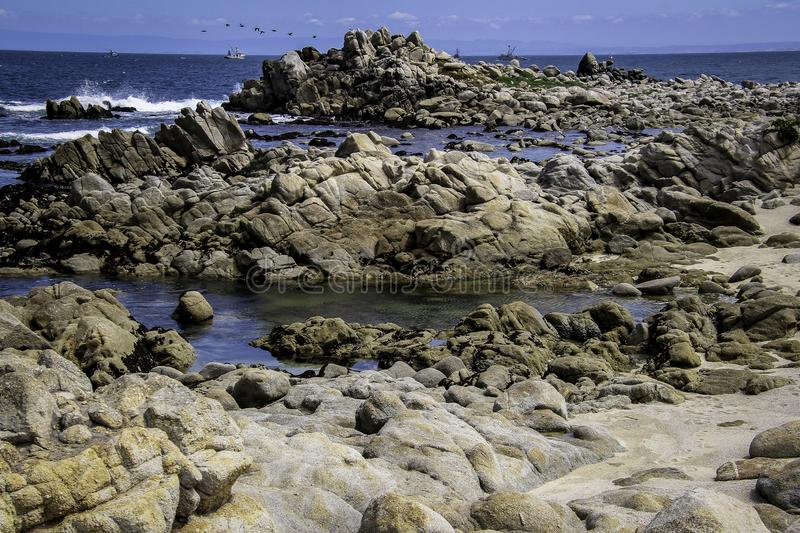 Rocky Seashore With Surf. Pacific Ocean textured rocks and blue water surf splash stock image