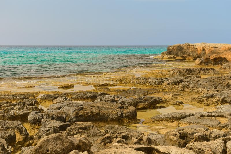 Rocky seashore with turquoise water royalty free stock photography