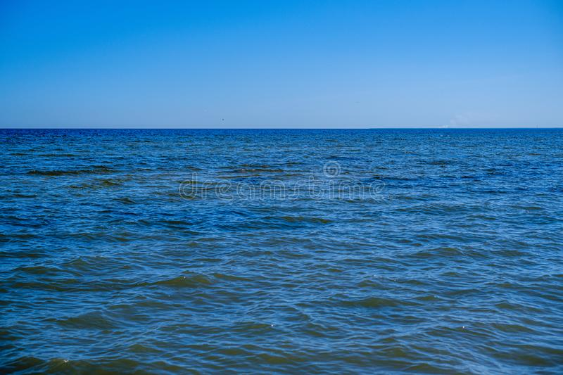 rocky seaside beach with blue water under summer sky stock photography