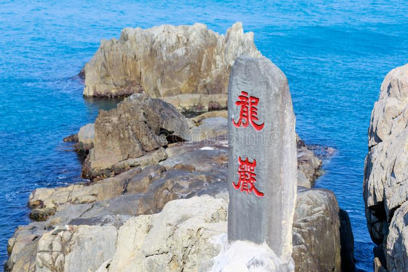 Rocky seaside of Haedong Yonggungsa Temple with a stone signage with the chinese calligraphy as Dragon Rocks in Busan stock images