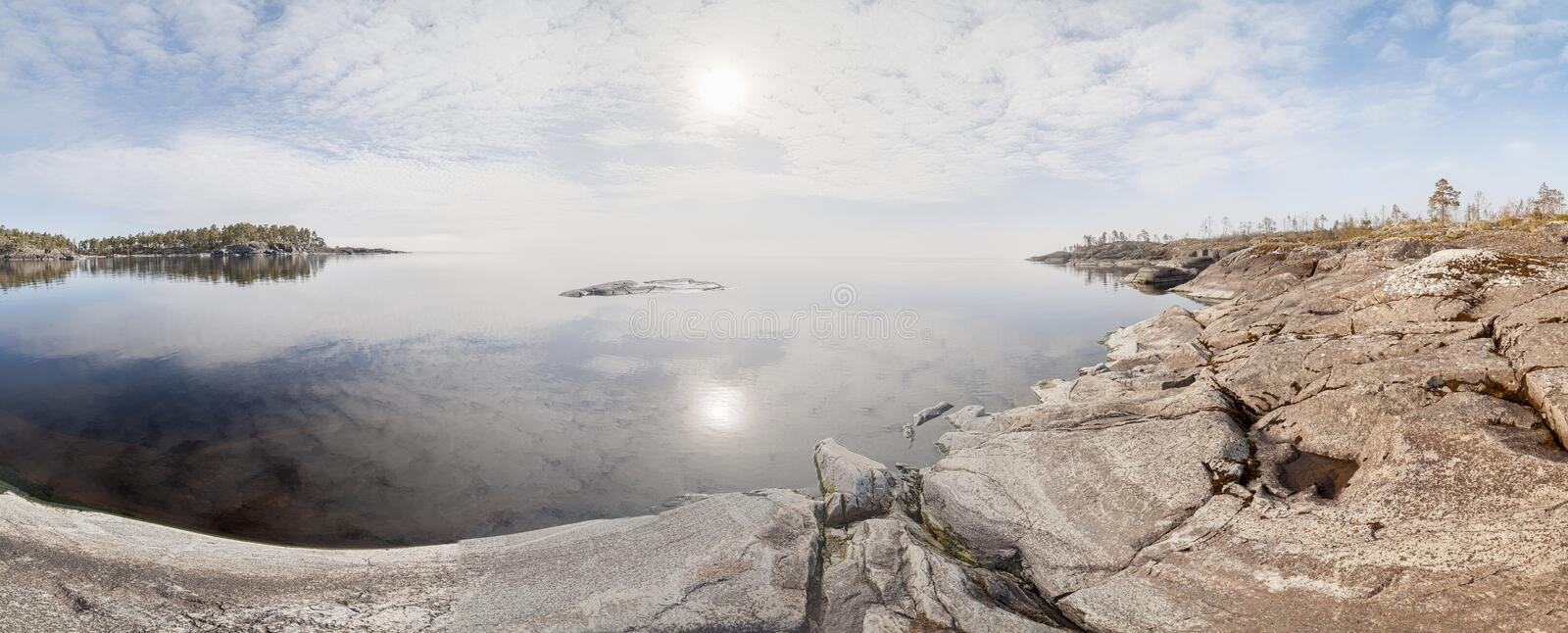 Rocky shore of the lake on a sunny day. royalty free stock photography