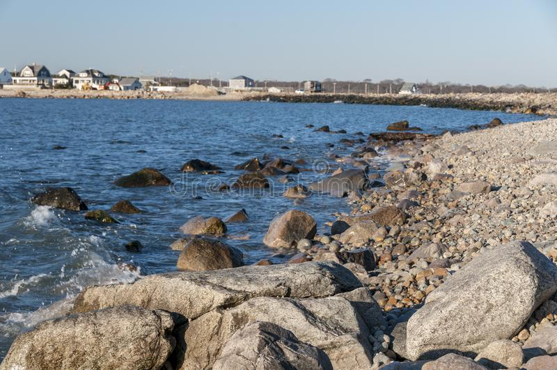 Rocky New England coast in Westport, Massachusetts. Rocky shore in late afternoon sun at Gooseberry Neck in Westport, Massachusetts with houses and causeway in royalty free stock photo