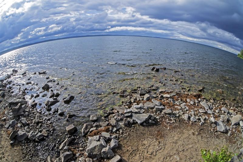 Rocky shore of the morning lake in cloudy weather in the southern Urals, lake Uvildy. Filmed lens fisheye royalty free stock images