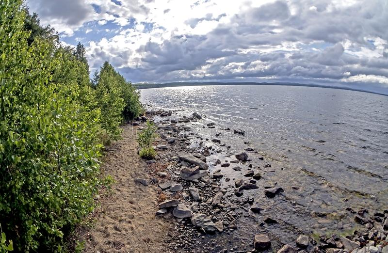 Rocky shore of the morning lake in cloudy weather in the southern Urals, lake Uvildy. Filmed lens fisheye royalty free stock photography