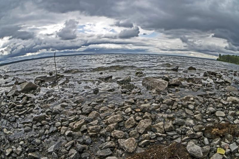 Rocky shore of the morning lake in cloudy weather in the southern Urals, lake Uvildy. Filmed lens fisheye royalty free stock photo