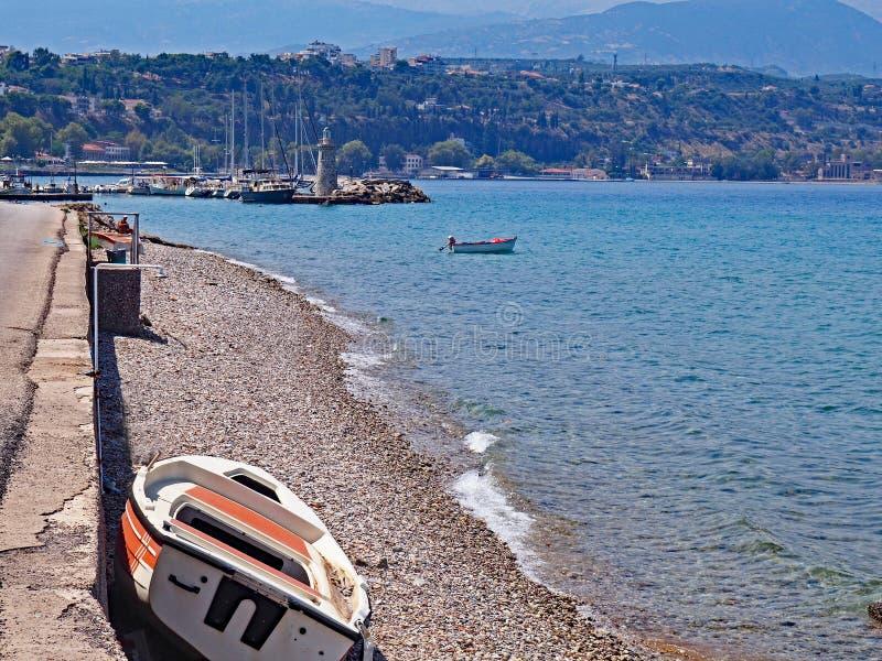 The rocky shore near Aigio, Greece on the Corinthian Gulf. A view up the coast of the Corinthian Gulf looking toward the town of Aigio, Greece stock photography
