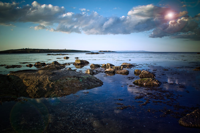 Rocky shoreline and clouds 2. A view along a rocky shoreline or coast with large, white and silver clouds in a blue sky royalty free stock photo