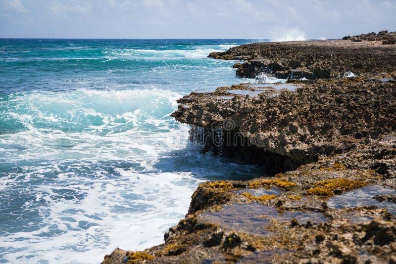 Rocky shoreline with crashing waves in aruba. Image of waves crashing against a rocky shoreline in aruba royalty free stock photo