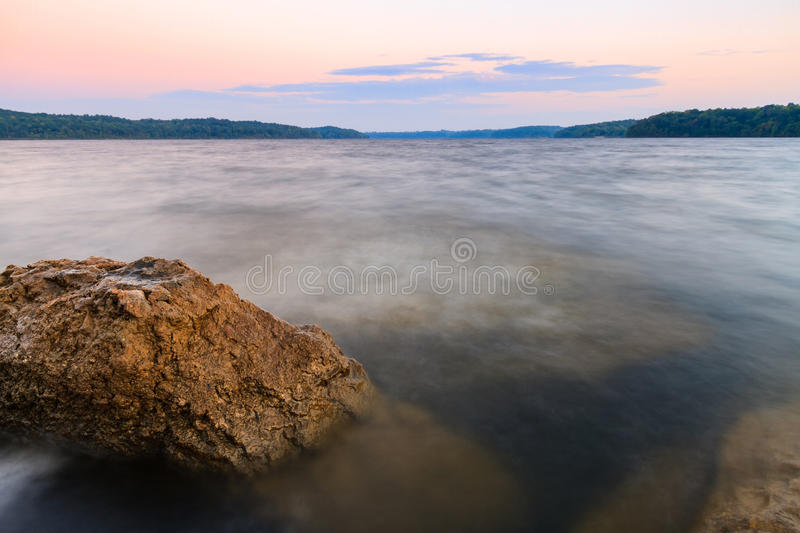 Rocky Shoreline of a lake at sunset royalty free stock photography