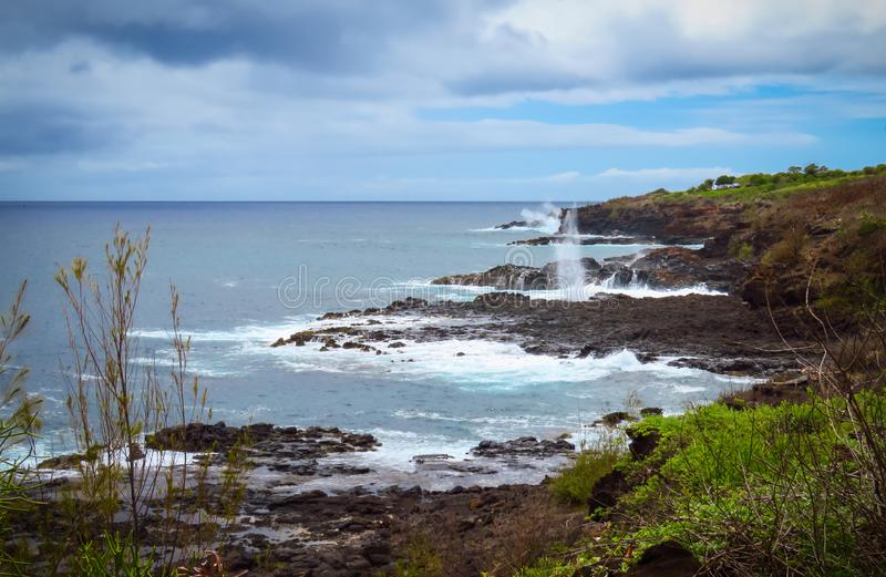 Rocky shoreline with Spouting Horn blowhole in the background, Kauai, Hawaii, USA. Seascape of the rocky shoreline with the Spouting Horn blowhole in the stock photo