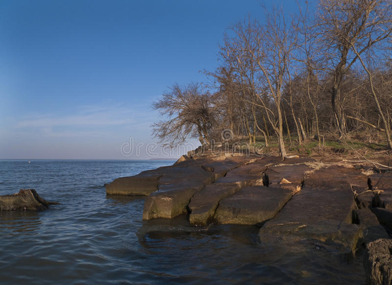 Rocky slabs of stone on the coastline of the Arkansas River. Slabs of a large rock formation on a large lake, landscape, seascape image, copy space, hills on the stock photos
