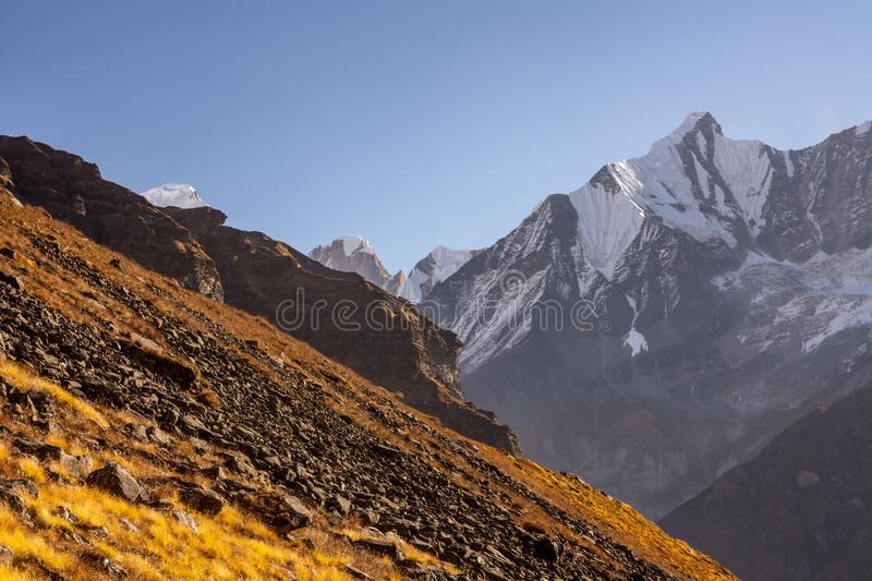 Rocky slope of orange color in contrast with snowcapped mountains in the Himalayas stock photo
