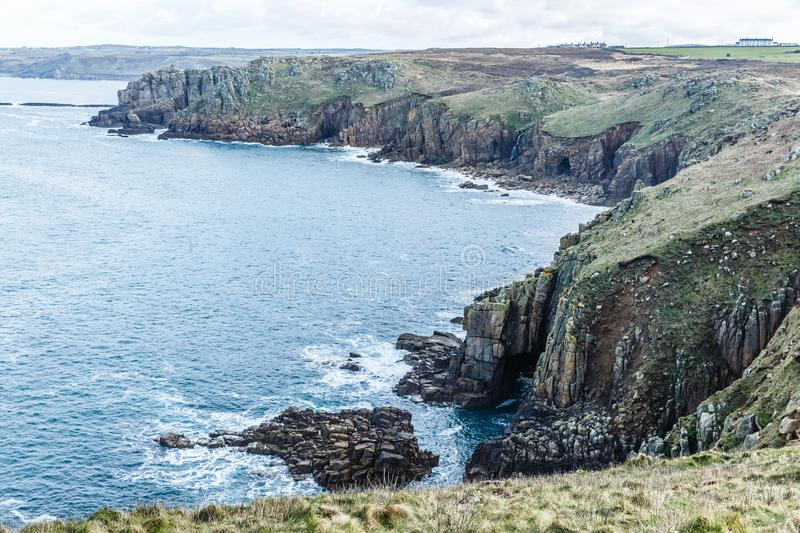 Rocky and steep shoreline. Along the sea; the coast and the farthest fields are green with spring grass; sea with light blue waters stock photo