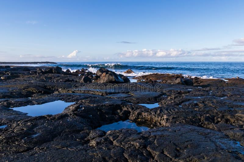 Rocky volcanic shoreline in Hawaii. Low tide; pools of water in rock cavities. Waves, ocean blue sky and clouds in background. stock photos