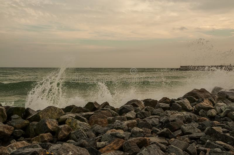 Rocky wild coast of the ocean. Waves with splashes breaking on the shore. deserted dock in the background. stock photo