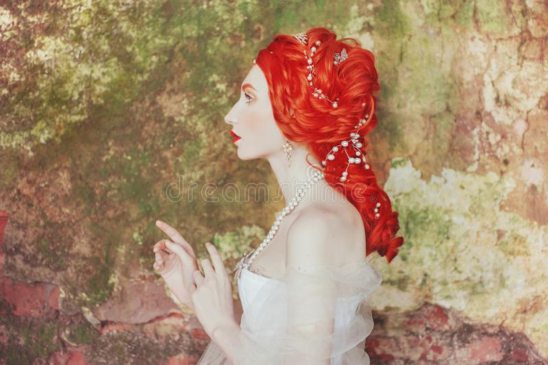 Rococo redhead princess with perming hairstyle. Fabulous ancient queen with historic hairdo against backdrop of stone wall. stock photos
