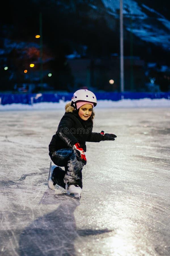 9 roczniak dziewczyny łyżew na lodzie w wieczór na illuminat obraz royalty free