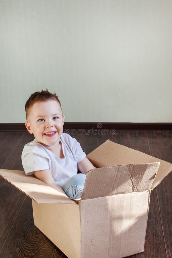 4 roczniaka blondynki chłopiec siedzi w pudełku i spojrzeniach przy kamerą w domu zdjęcia royalty free