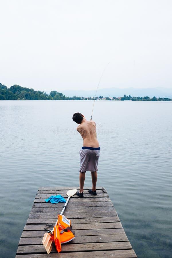 12 roczniaka chłopiec połów na jeziornym molu obraz stock