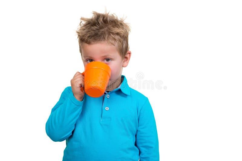 3 roczniaka chłopiec w błękitnych punktach pije od kubka, odosobnionego na bielu fotografia royalty free