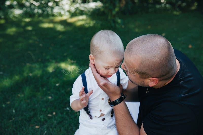 2 roczniaka dziecko w parku w białych skrótach i białej koszulce z tatą, Blond ch?opiec z niebieskimi oczami Rozochocony dziecko obraz stock