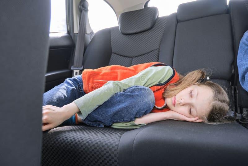 9 roczniaka dziewczyny dosypianie w samochodzie, dziecka lying on the beach w tylnym siedzeniu pojazd zdjęcia stock