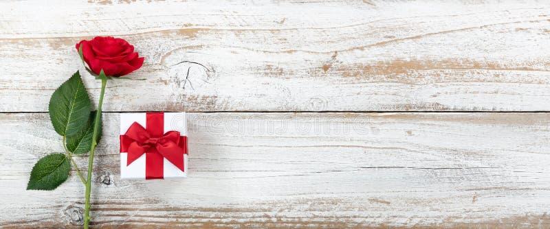 Rocznicowy tło z pojedynczym czerwień prezenta i róży pudełkiem na bielu wietrzał drewno obraz stock