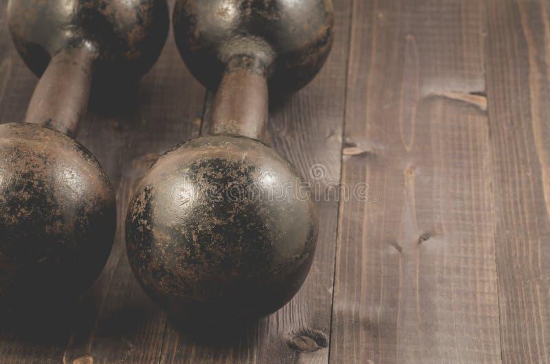 Roczników żelazni dumbbells na tle, roczniku ir czarnych drewnianych/ obraz royalty free