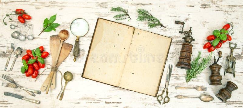 Roczników kuchenni naczynia z starą książką kucharska, warzywami i ziele, obrazy royalty free