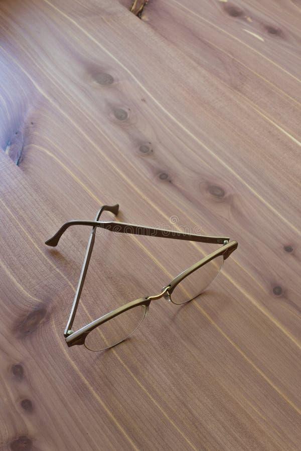 Roczników mężczyzna uzbrajać w rogi rimmed stylowych eyeglasses na neutralnym drewnianym tle zdjęcie stock